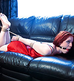 Redhead hogtied on the coach and ball-gagged