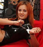 Sexy dressed redhead plays with handcuffs