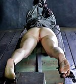 Straightjacketed, silenced with a ball gag, plugged, caned