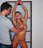 Barra cuffed and strapped to metal rack, ball-gagged, tit-grabbed