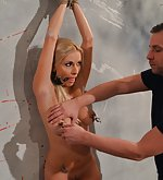 Susane struggling against the wall, ball-gagged, nipple-clamped