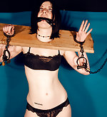 Brunette stocked, cuffed, chained, gagged