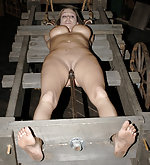 Caged, locked into the stocks and dildoed