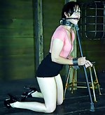 Brunette cuffed, metal-gagged and tits-clamped