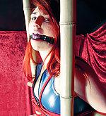Latex redhead in bamboo bondage